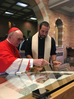 Cardinal Stafford blessing the St. John's Bible display cases.